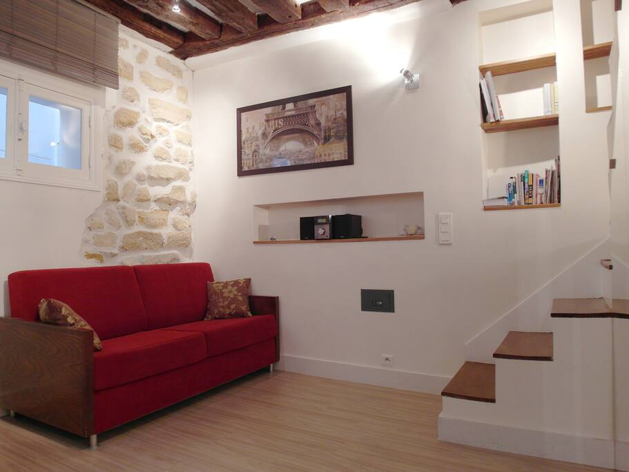 Authentic exposed stones wall and visible beams in the living room