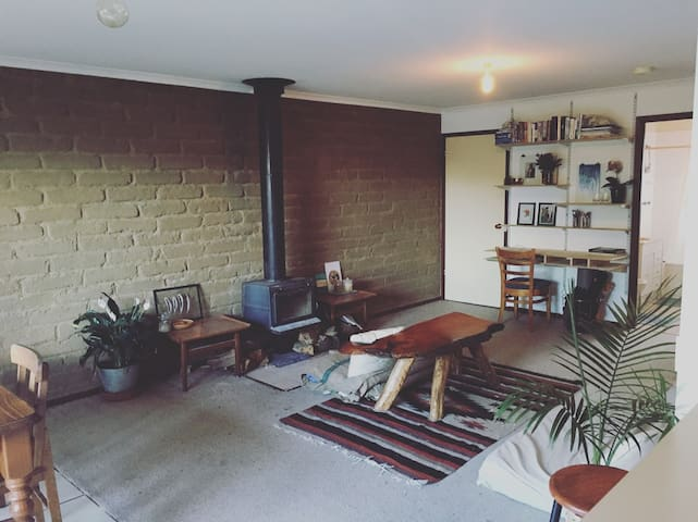 Living room with stove, couch, desk and dining table