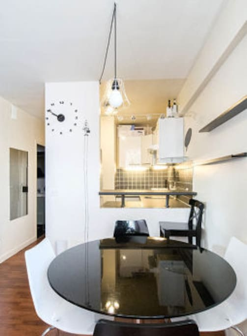 Dining area with a bar overlooking a fully equipped kitchen.