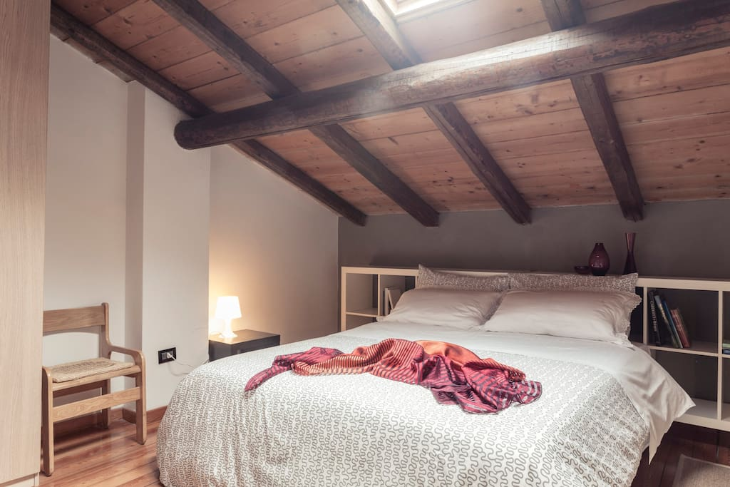 Un romantico lettone sotto un tetto in travi di legno, e abbaino per veder le stelle!