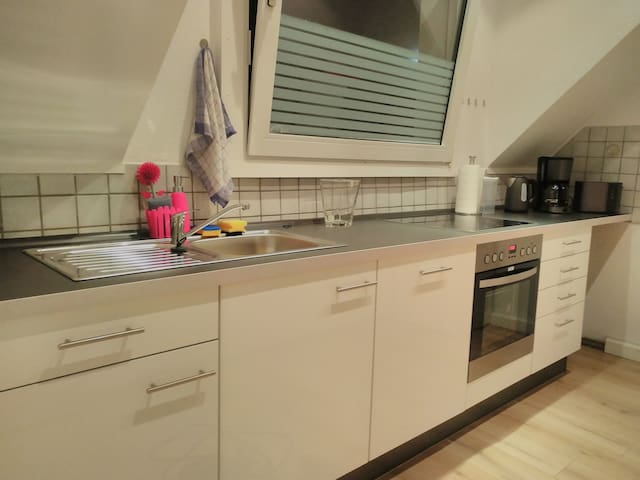 Voll ausgestattete Küche mit Geschirrspülmaschine, Ceran-Kochfeld, Herd, Wasserkocher, Kaffeemaschine, Toaster, Mikrowelle und Grundausstattung zum kochen.