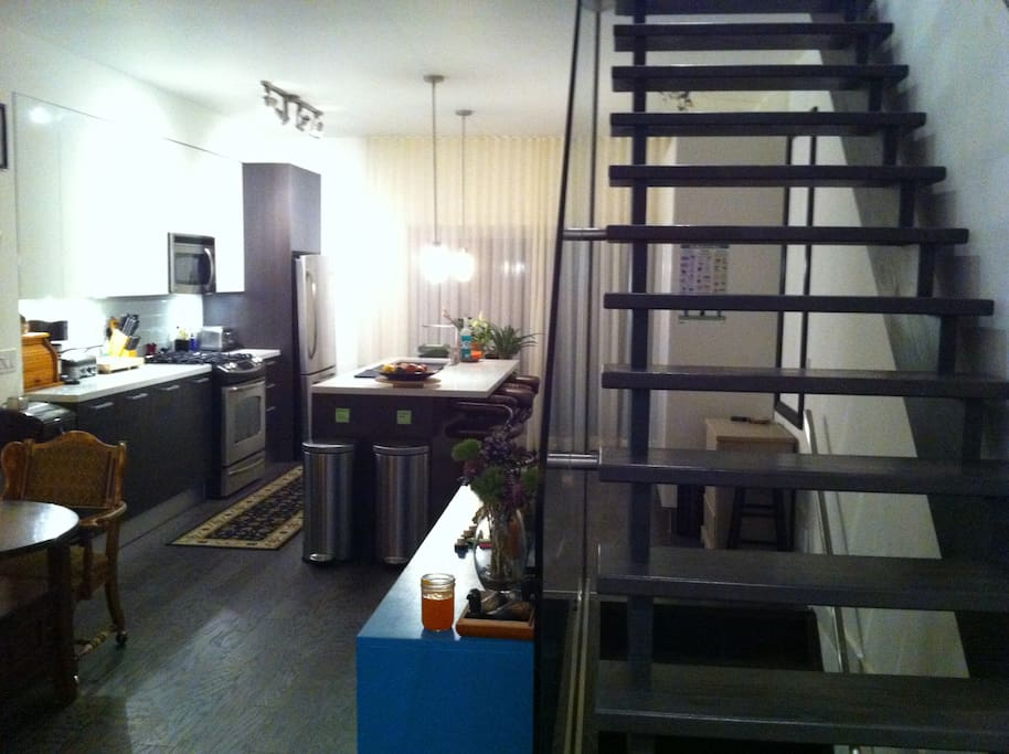 View of kitchen and stairwell from home entrance.