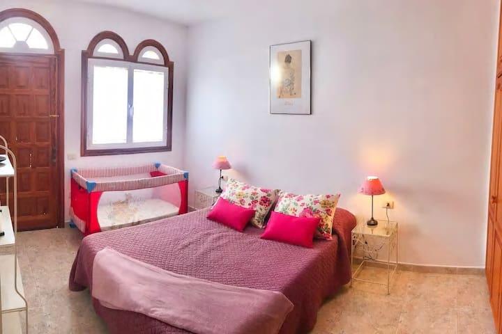 Dormitorio con cama de matrimonio y cuna para bebés.