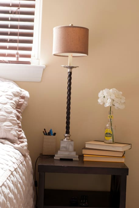 This room is simply decorated with calming tones of white and brown. Natural light fills the room by day and the warm glow of the lamp by night. The dark blinds help keep the street lights out for a restful and undisturbed sleep.