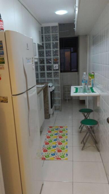 Cozinha com fogão , microonda ,  freezer , cafeteira ,  geladeira , área de serviço com máquina de lavar roupa ,  tanque e banheiro