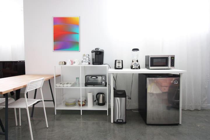 Petit coin cuisine avec équipement de base. Mini-frigidaire, machine à café Keurig (café fourni), micro-onde, bouilloire, grille-pain, mini-four. Tout autre appareil de cuisine ou autre qui ne sont pas sur place sont interdits. (À noter que le mixeur n'est plus sur place.)