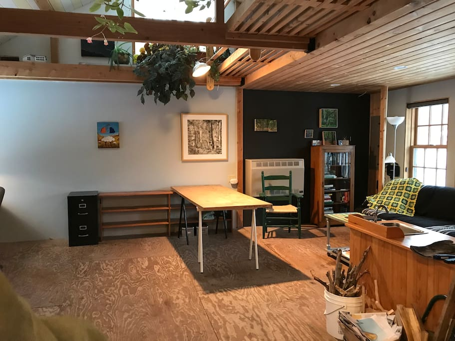 Studio and Sitting Room, the central area of the 22' x 33' Saphouse, a farm building under renovation as a studio and artist's home.  15' ceiling.  Plants decorating the loft. Durable plywood floor.