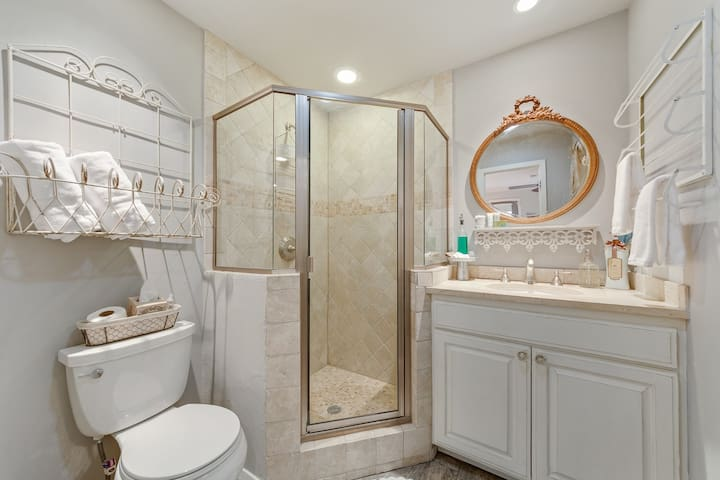 Large rain head shower with natural bath products and lots of fluffy towels.