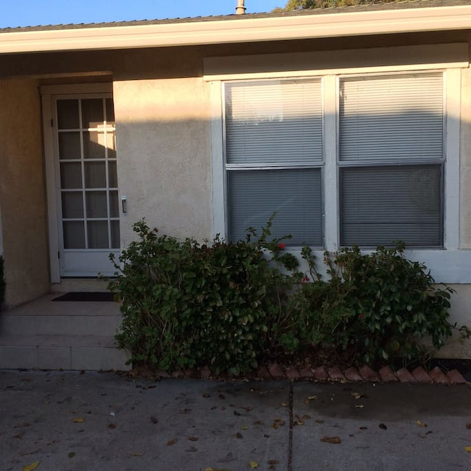 Front of the charming home. Has plenty of secured parking. Has long driveway , fenced with lovely trees and plants.