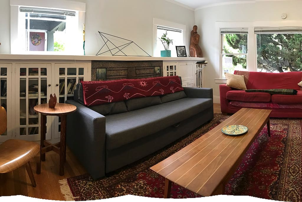 Living room. Three comfy sofas and warm colors. Light everywhere. Apartment can sleep two in bedroom sleep number bed, two on this new gray sofa with memory foam topper, one in twin daybed - new Sealy mattress, one on red couch,  two on an Aerobed.