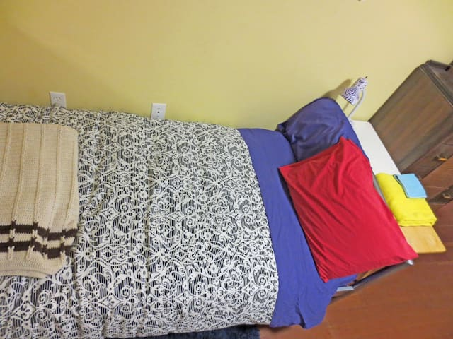 Quiet room has two separate twin beds for two friends to rent. All the linen is color blocked.