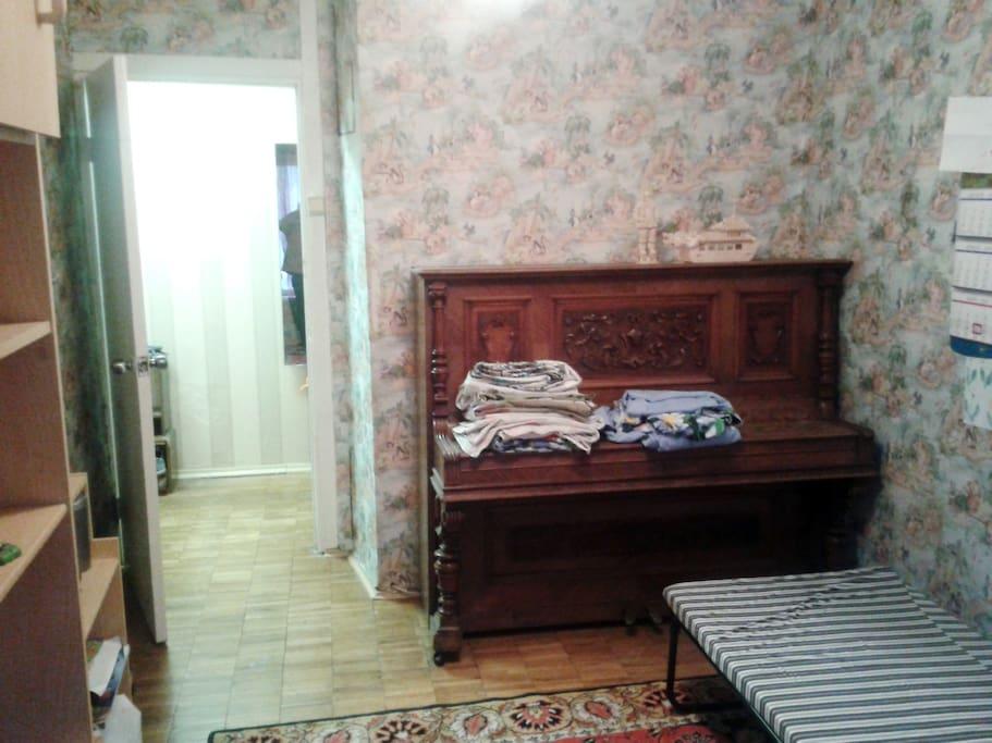 Маленькая комната с корпусной мебелью из шкафа, стеллажей и стола. Плюс к тому - невыносимое, в прямом смысле слова, но красивое пианино работы начала прошлого века, некогда украшенное бронзовыми подсвечниками )