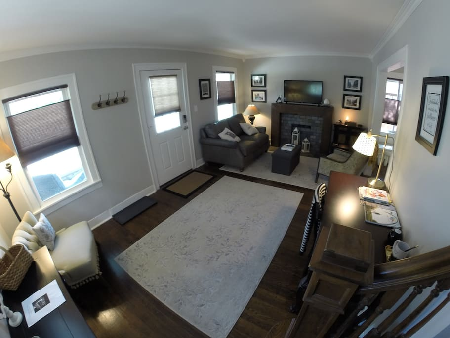 Wide angle shot of living room with seating area, reading nook, desk, and coat rack