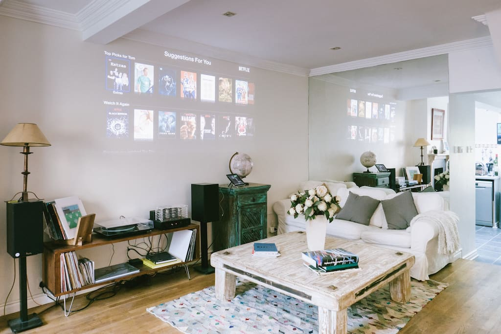 Living room with projector featuring Netflix, Apple TV