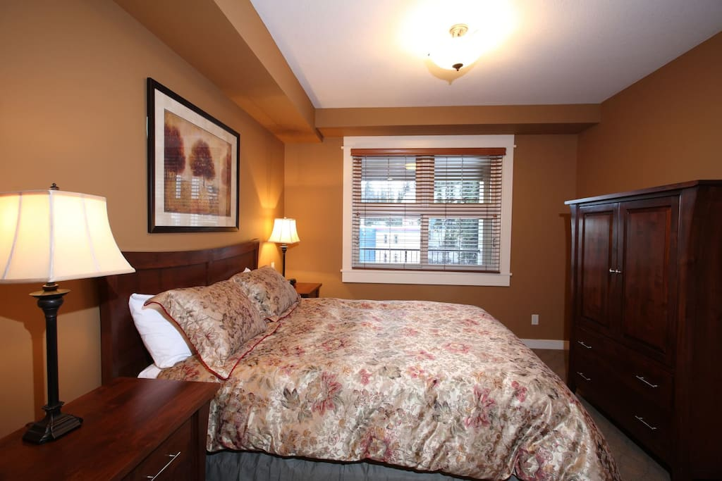 The bedroom features a king or queen bed and ample wardrobe space