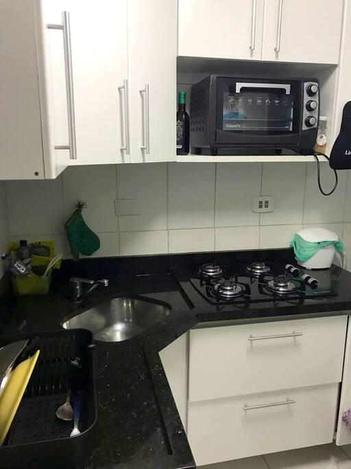 Cozinha com forno elétrico, microondas e geladeira.