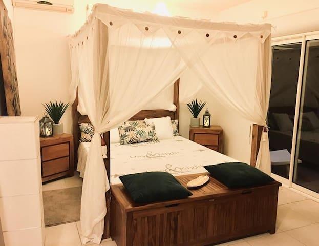 L 'espace nuit avec un grand lit double baldaquin en bois de Bali et sa moustiquaire sur mesure.