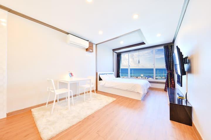 (4)302호 침실룸_깨끗한 침구류와 창문너머 바다뷰가 보이는 숙소
