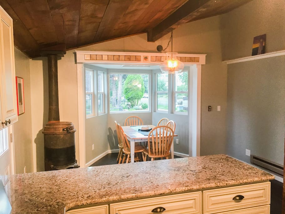 Kitchen space with a family table seated for six. Great natural light and view of quaint neighborhood