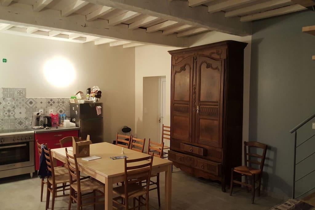 Grande pièce à vivre avec une cuisine ouverte.
