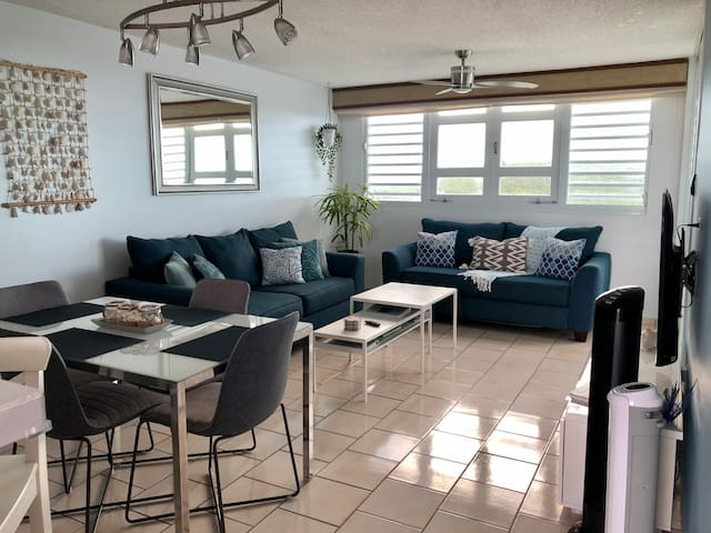 """Spacious living room with two sofa beds, dining table, breakfast bar, NEW 55"""" roku tv with guest Netflix, WiFi, books, games, ceiling fan with remote control, and oscillating tower fans. Feel the cross breeze or step out onto the balcony from here."""