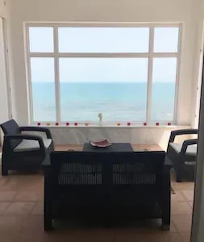 Un salon (entièrement vitrée)  face mer vous permet de profiter de la vue sur la baie tout en étant confortablement installé