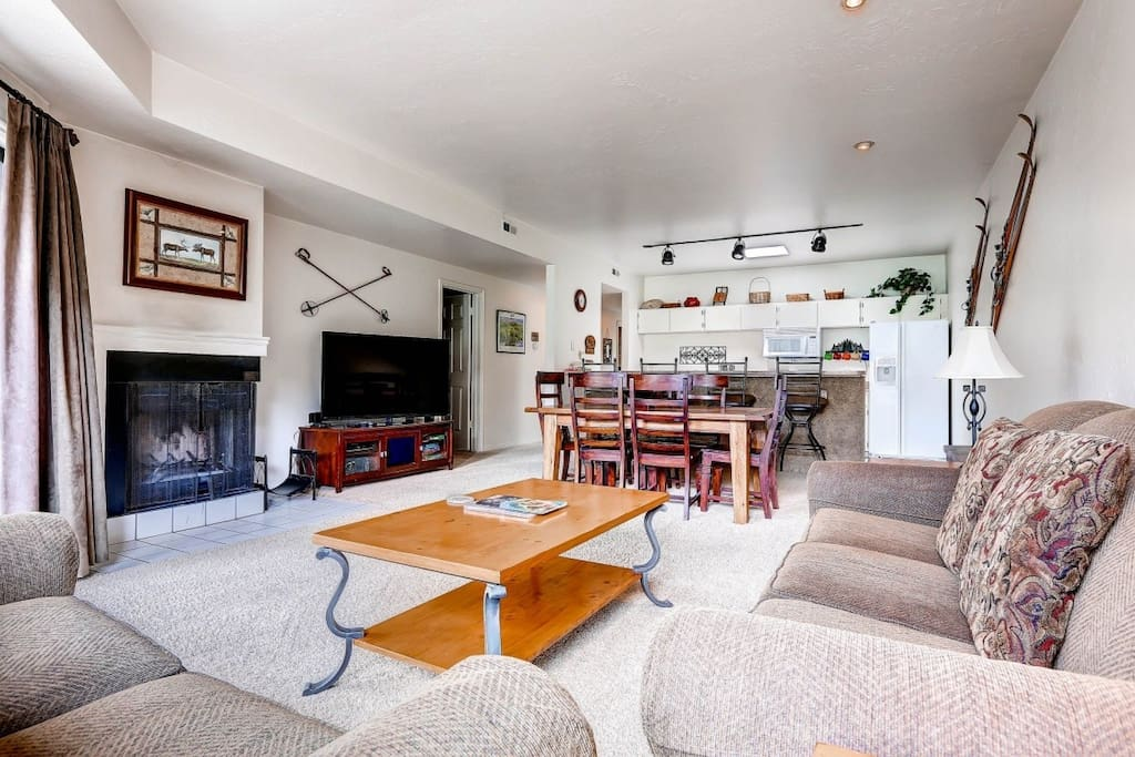 Living room has spacious seating for five (5), wood burning fireplace, sleeper sofa and south-west facing mountain views from the private balcony.
