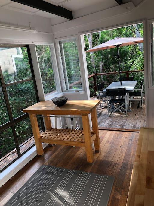 Standing in the kitchen looking out to private deck in the forest