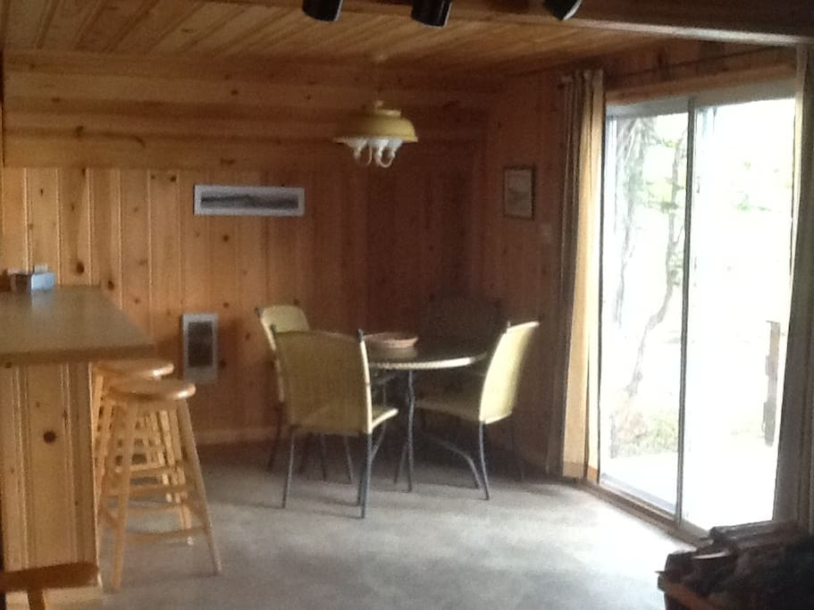The dining/kitchen area with patio doors to the deck overlooking the lake.