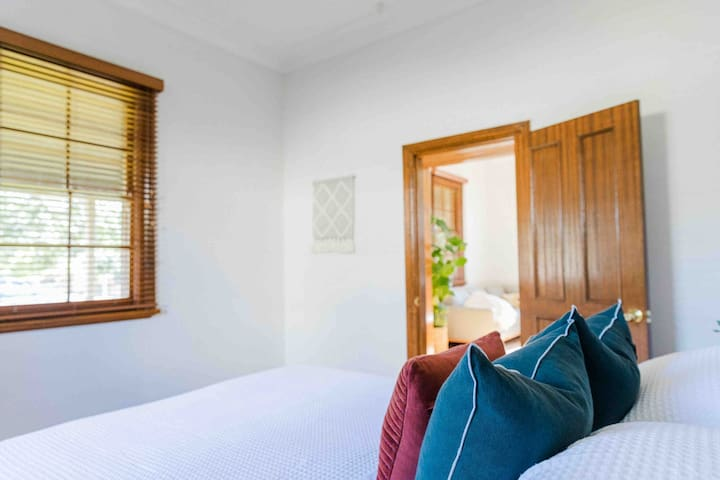 This bedroom is located downstairs opposite the lounge area and home entrance. A spacious room to move with windows looking out into the front verandah.