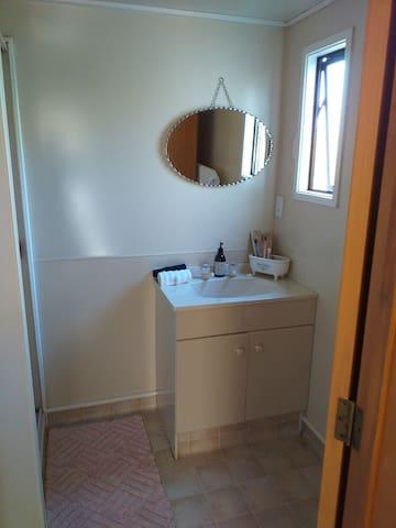 Bathroom including shower and heated towel rail.