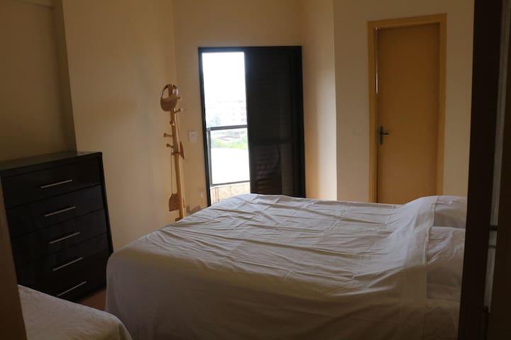 Suite com cama queen, mais uma cama de solteiro, comoda e um cabideiro.  varanda com vista da praia.