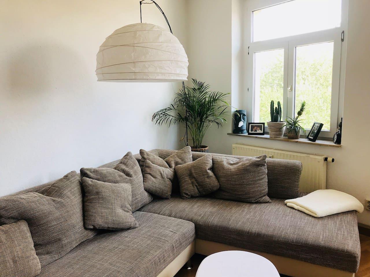 Das Wohnzimmer mit einer wirklich großzügigen Couch! Wenn ihr mehr als 2 Personen seid, findet hier auf jeden Fall auch noch einen Schlafplatz!