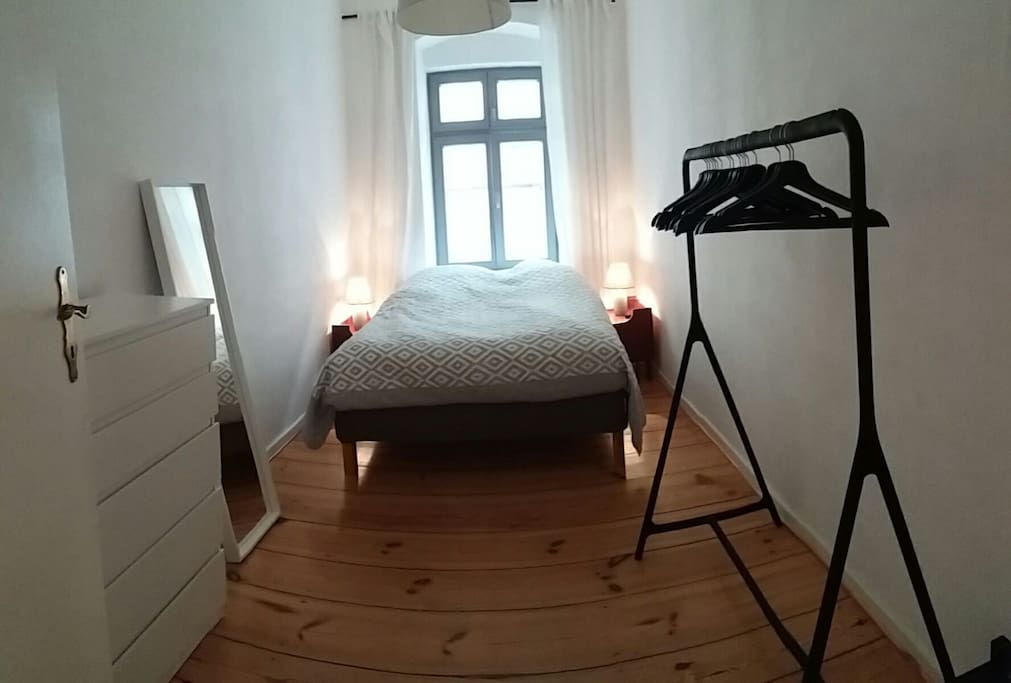 Bedroom with double bed, two hangers, a draw and a shelve