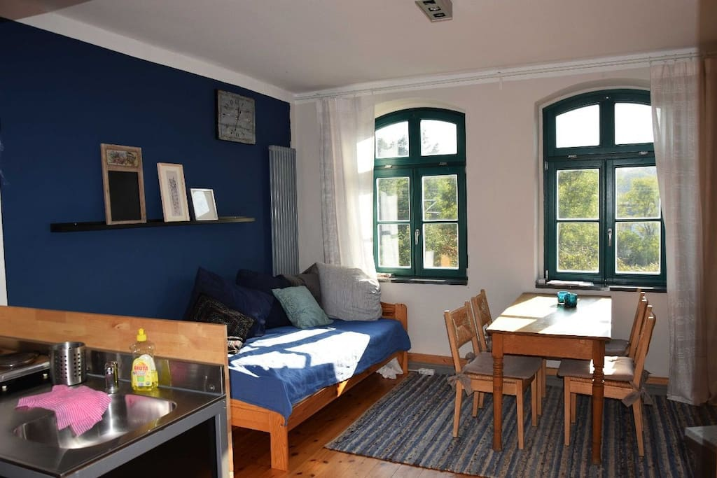 Wohn-/Essraum mit kleiner Kochecke und Bett für die 3. Person