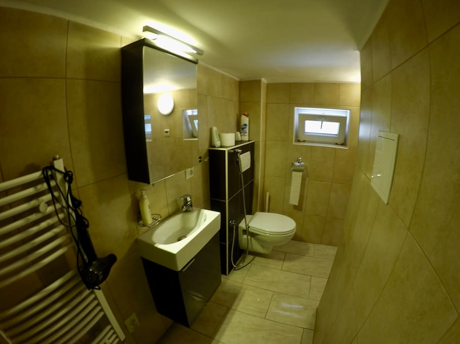 The bathroom is quite small with the little sink, shower and toilet. Enough to stay clean during your stay:)  We use floor heating, if you still feel cold, there is a heater you can use too. Little step with lower overhead when entering the bathroom.