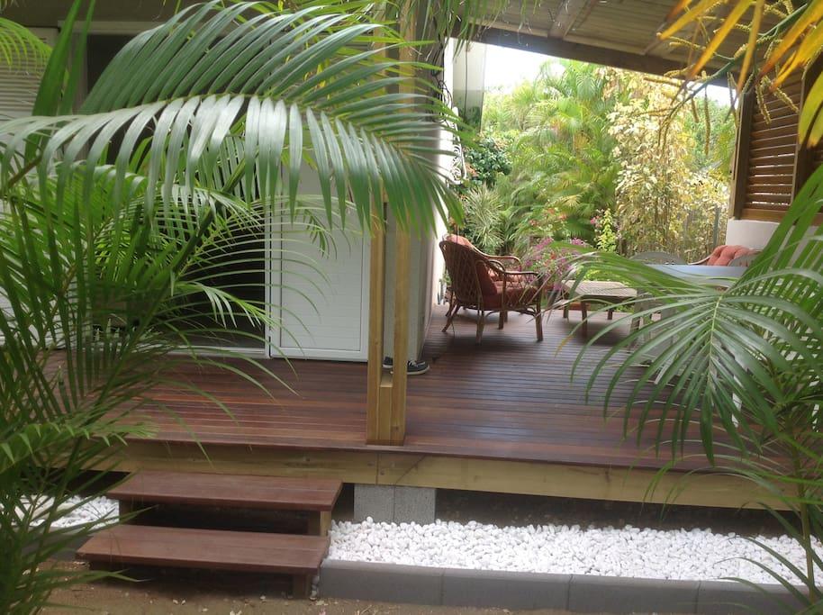 varangue en bois donnant sur jardin verdoyant