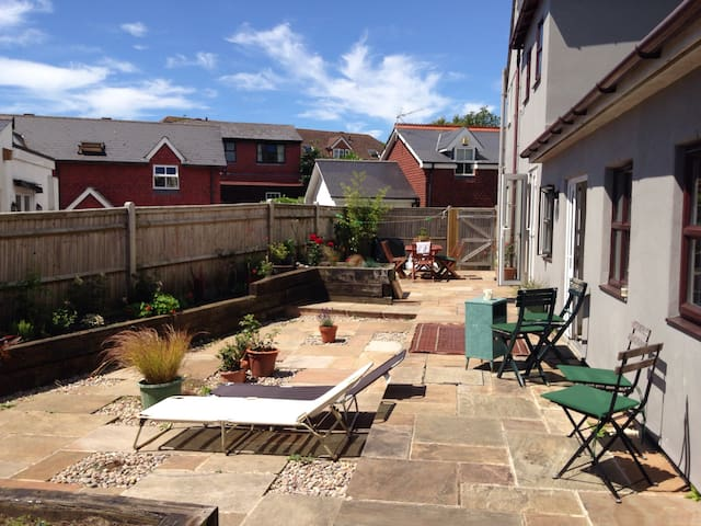 South facing, with beautiful flowers, outdoor seating and loungers.