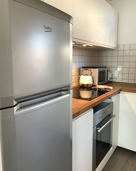 Full size refrigerator, cooktop, oven and microwave.