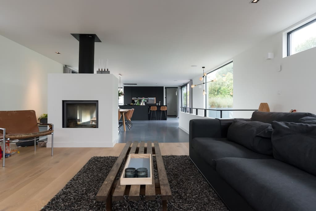 Living room on the top floor with sea through fire place in front - wall side to the right on this photo