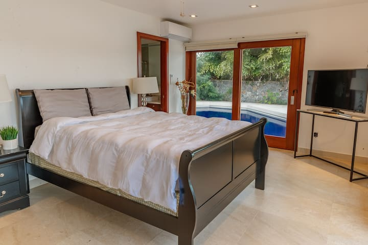 King bed, TV and doors that open out directly to your private pool.