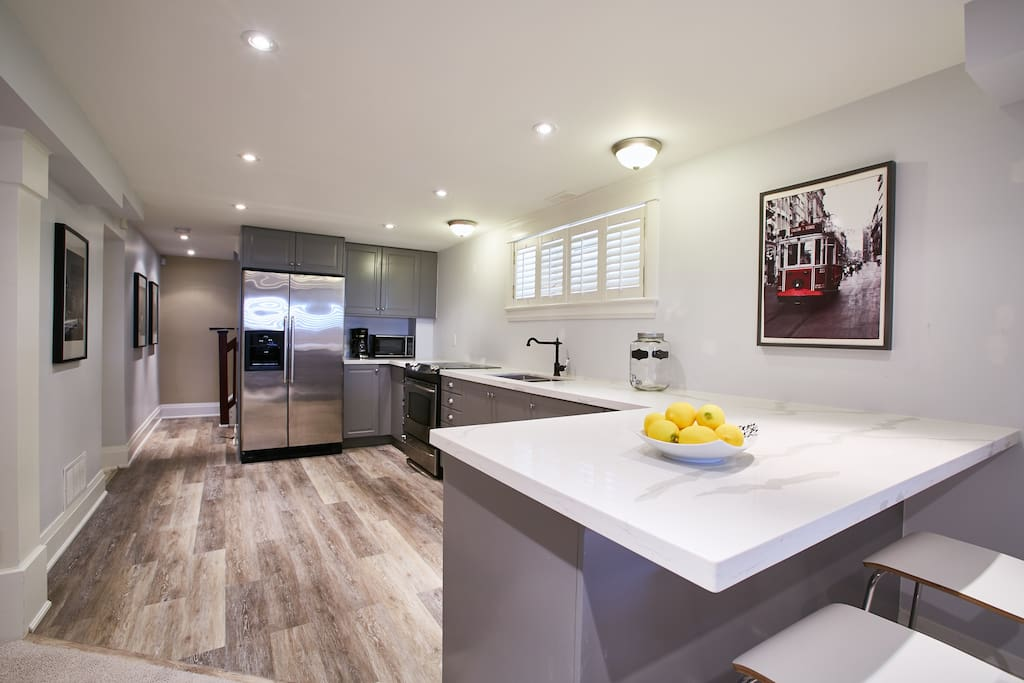Brand new large kitchen with quartz eat in bar and stainless steel appliances.