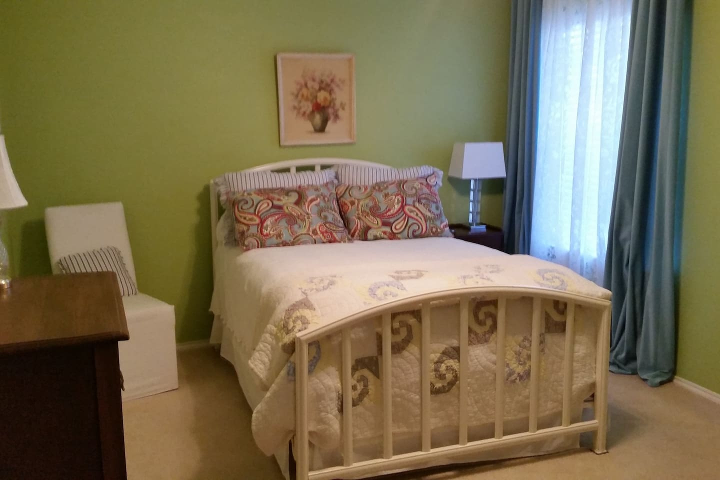 Cheery bedroom with comfortable double bed and TV.  Private bathroom is to the left of bed.