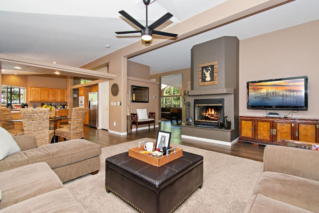 Large open floorplan with vaulted ceilings, panoramic windows, cozy fireplace & Direct TV.