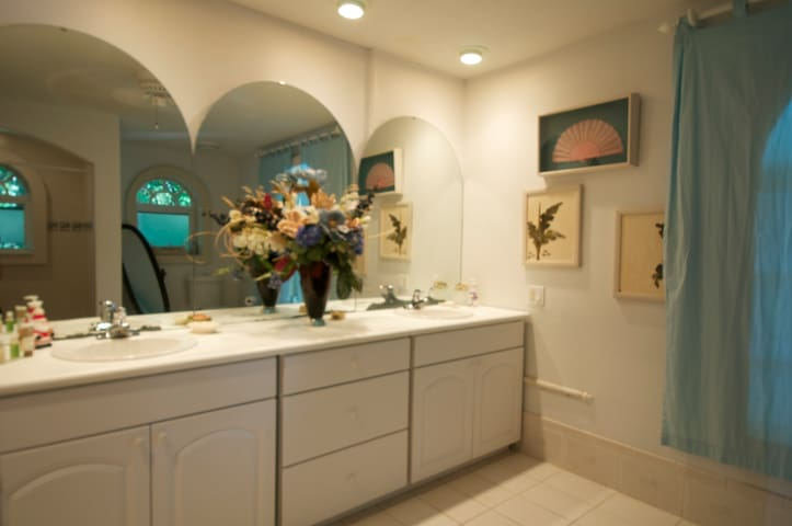 Double bowls with large beautiful white tile arched window.