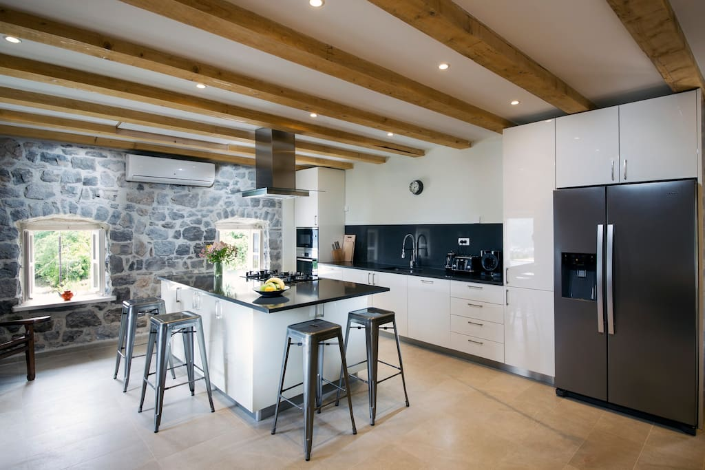 The modern kitchen is fully equipped with contemporary appliances and top quality glassware, pots, pans and plates