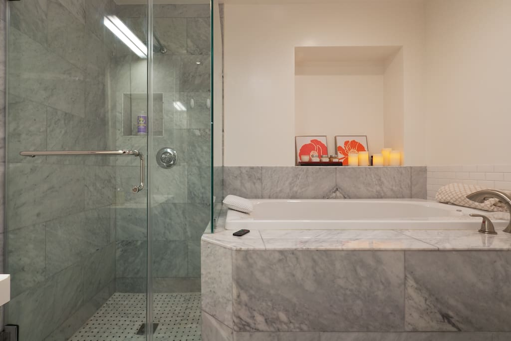 Stand-alone, rainfall shower. Marble tiles and glass shower door.