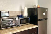 Fully stocked mini kitchen. All basic amenities and more. Fridge full of water bottles, a hot plate incase you need to cook or warm something up, coffee maker, electric water kettle for tea, toaster, toaster oven, microwave, dishes, silverware