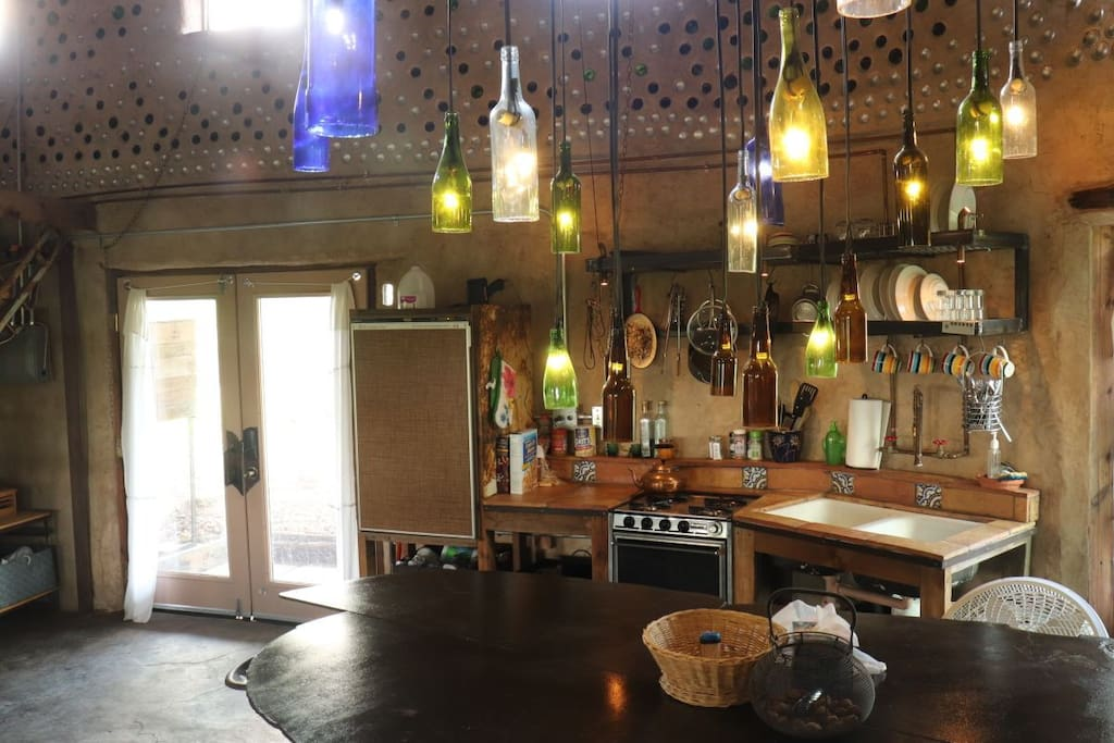 Here is a wine bottle chandelier that was crafted to be the main light source of the kitchen.