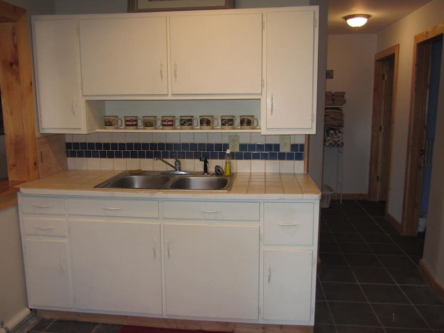 Kitchen has sink, stove, frig, microwave, toaster, dishwasher; bathrooms are down the hall.